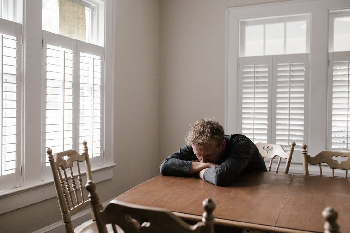 a man struggling to navigate his thoughts at a dining table