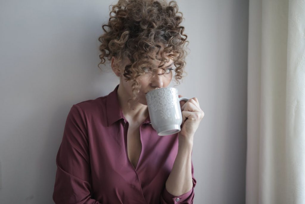 a woman drinking a hot beverage as she muses about 2021