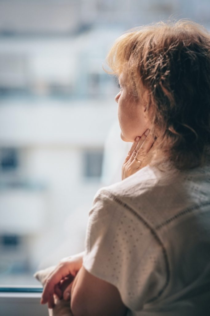 a woman feeling anxious and uneasy as she gazes outside the window