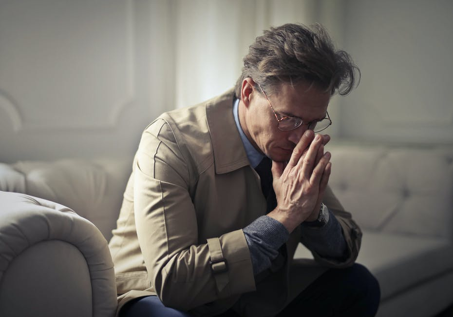 A man looks down, seeming worried and stressed out with his hands against his face