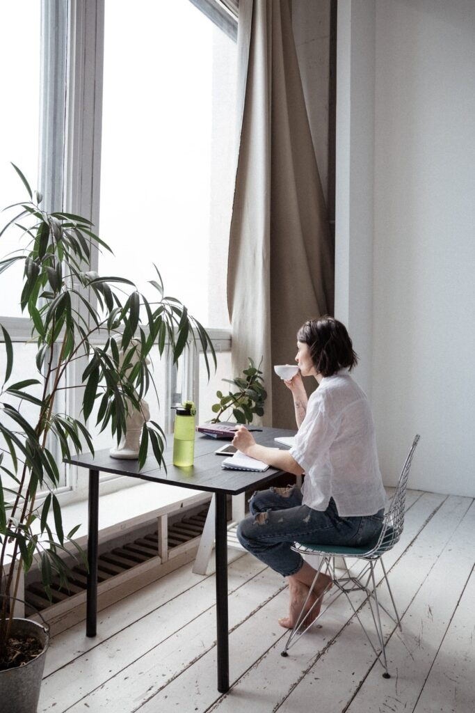 a woman sipping tea in her home office