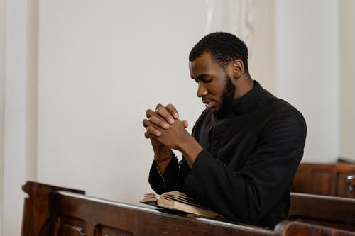 A man prays and reads the bible intently while sitting in a pew